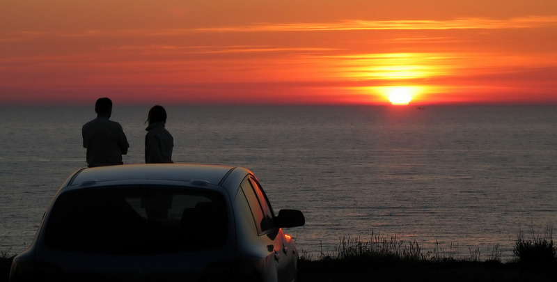 Car with man and woman watching sunset