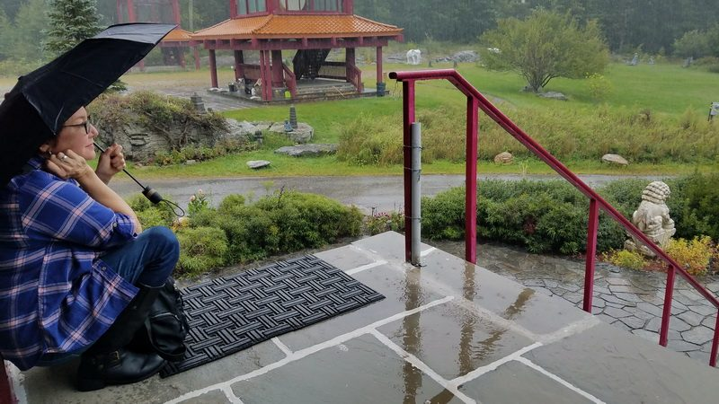 Elaine reflecting in the rain at Guan Yin temple at Chuang Yen Monastery