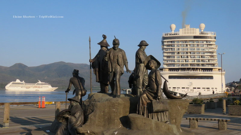 Dockside scene with historical statues dwarfed by cruise ships